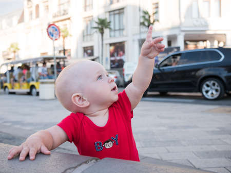 Young mother with her toddler son playing outdoors in city. Stock Photo