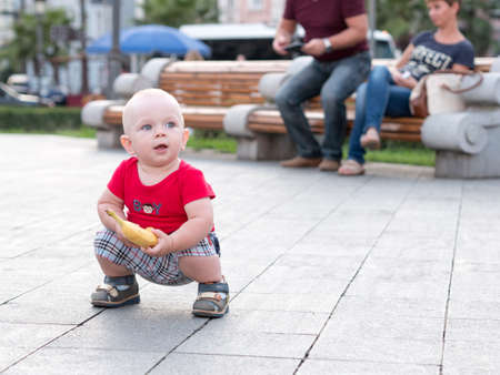 babysit: Young mother with her toddler son playing outdoors in city. Stock Photo