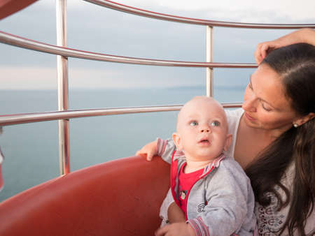 Young mother with her toddler son playing outdoors on Ferris wheel. Stock Photo