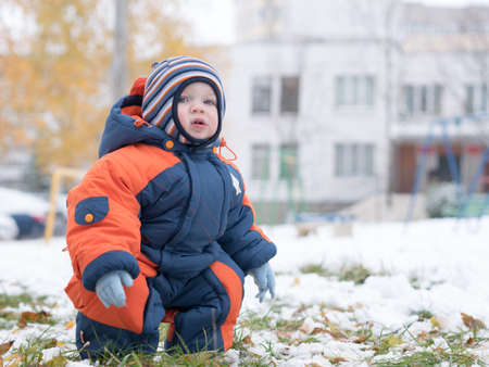 Attractive baby boy playing with the first snow. He smiles and looks snowman. Thick blue-orange jumpsuit and bright striped hat on a year-old child
