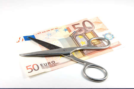 accrual: A 50 euro Bill  and scissors isolated on a white backround.