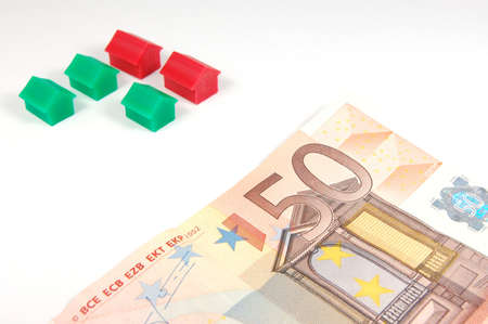 mortage: Some Houses and money isolated on white backround. Stock Photo