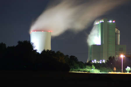 a smoking industrial power plant at night photo