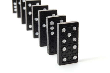 risky: chain of dominoes isolated on a white background Stock Photo