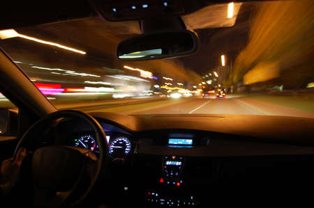 action blur: night drive with car in motion through the city shows the speed