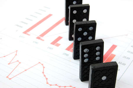 banking crisis: domino over business chart showing the risk of financial or banking crisis