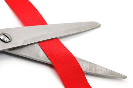 unveil: scissors and red ribbon isolated on white showing a ceremonial opening