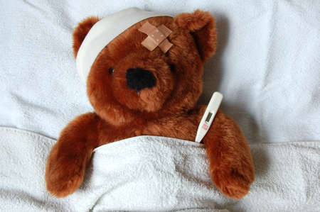 sick teddy bear with injury in a bed in the hospital Stock Photo