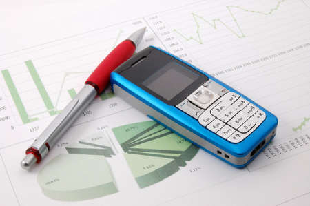 blue cell phone over business chart showing success photo