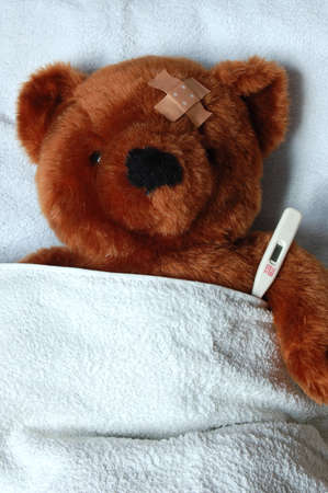 doctor toys: sick teddy bear with injury in a bed in the hospital Stock Photo