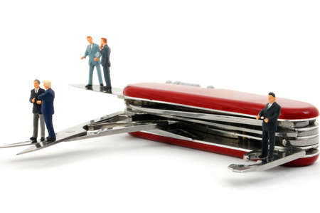 swiss knife: business people on penknife isolated on white background