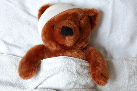 sick teddy bear with injury in a bed in the hospital photo