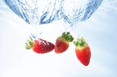 healthy strawberry fruits splashing in cool water photo