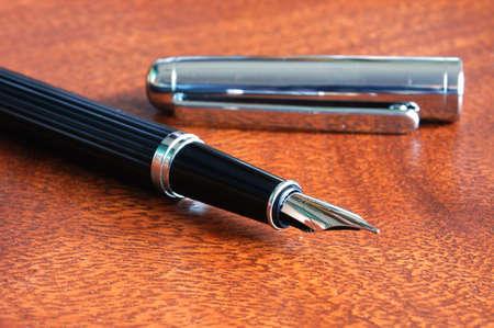 ball pen: business fountain pen on a wood desktop in an office