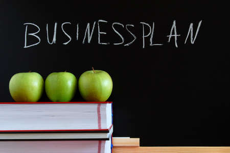 business blackboard with apples and books and space for a message photo