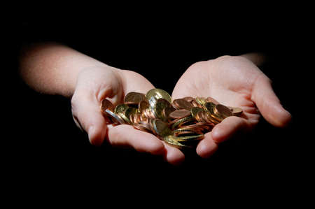 hands with money coins on a black background photo