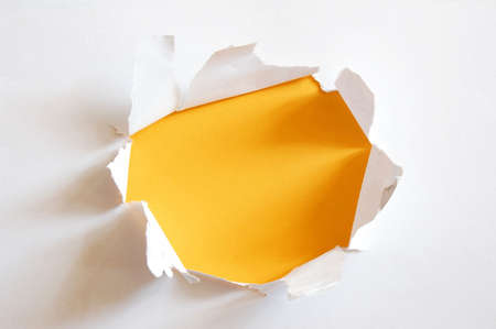 penetration: yellow hole in blank sheet paper with copyspace Stock Photo