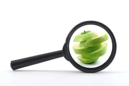 sliced apple: magnifying glass and sliced apple isolated on white                                     Stock Photo
