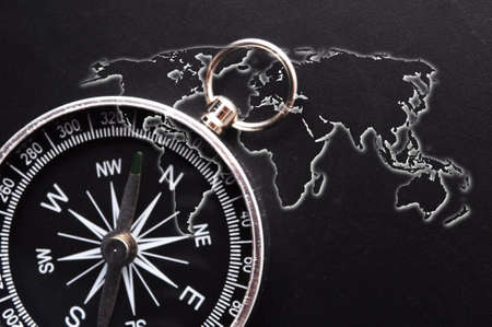 world map and compass showing business guidance concept