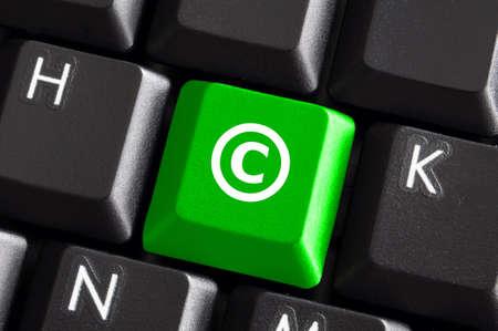 Copyright concept met groene knop op computer toetsen bord