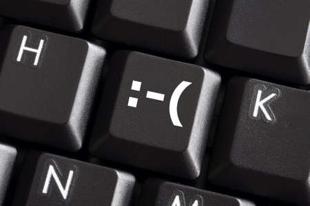 negative smilie on computer keyboard button showing bad feelings concept photo