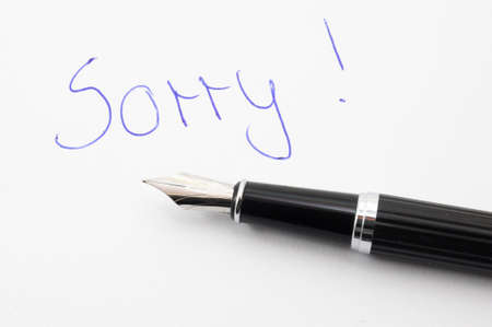 i am sorry: say sorry with a text message on paper and pen Stock Photo