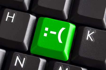 negative smilie on green computer keyboard button showing bad feelings concept photo