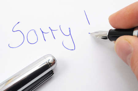 apology: say sorry with a text message on paper and pen Stock Photo