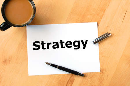investment strategy: business or investment strategy concept with pen paper and coffee in office