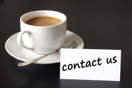 write us: contact us and coffee cup showing business support concept