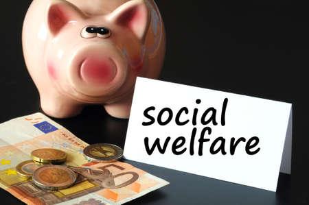 social welfare concept with money and piggy bank on black background Banco de Imagens