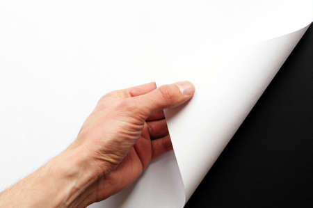page turn: page or blank sheet of paper with hand and copyspace in the corner