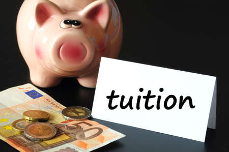 education tuition concept with piggy bank on black background Stock Photo