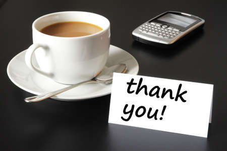 thank you or thanks concept with cup of coffee on black background photo