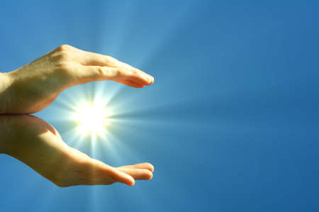 sunbeam: hand sun and blue sky with copyspace showing freedom or solar power concept