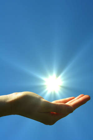 renewabel: hand sun and blue sky with copyspace showing freedom or solar power concept