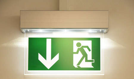green emergency exit sign showing the way to escape  photo
