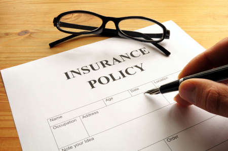 policies: insurance policy form on desk in office showing risk concept