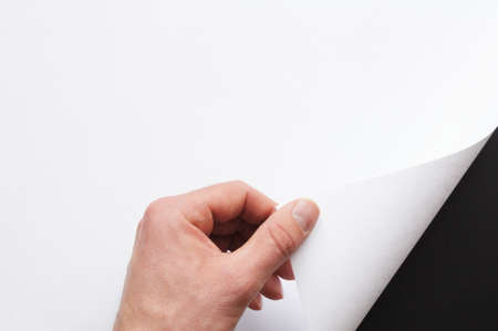 turn: hand turning over blank sheet of paper Stock Photo