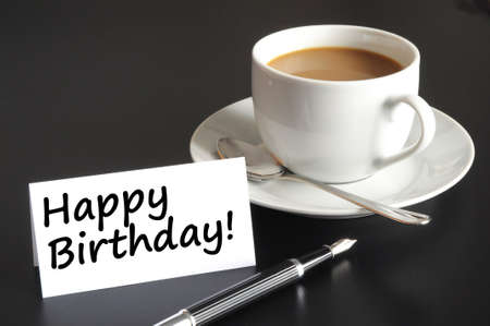 happy birthday greeting card with cup of coffee on black photo