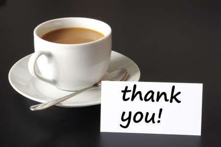 motivate: thank you or thanks concept with cup of coffee on black background