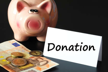 non cash: donation or donate concept with piggy  bank on black background