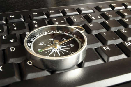 computer keyboard and compass showing internet navigation concept photo