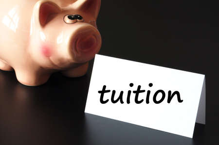 tuition: education tuition concept with piggy bank on black background Stock Photo