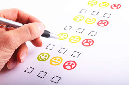 customer survey: hand pen and checkbox or tickbox with smilie