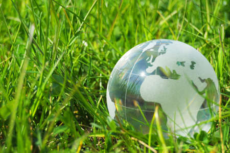 recycle glass: glass globe or earth in green grass showing eco concept with copyspace Stock Photo