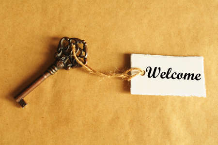 welcome concept with old grunge key and label or tag photo