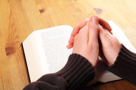 betende h�nde: Betende Hand und Buch auf Schreibtisch zeigt Religion-Konzept