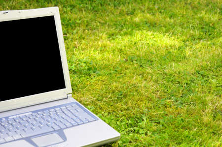 laptopn in green grass with blank or empty screen for copyspace photo
