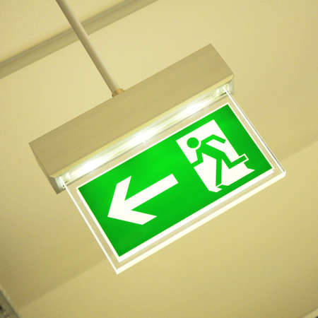 escape: green emergency exit sign showing the way to escape  Stock Photo
